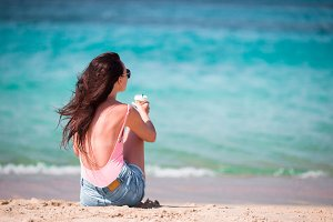 Young beautiful woman with coffee on the beach during tropical vacation. Girl enjoy her wekeend on one of the beautiful beaches in Mykonos, Greece, Europe.
