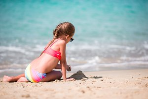 Adorable little girl drawing on sand at beach during summer vacation