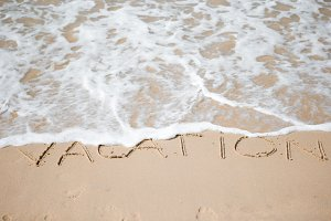 Vacation written on tropical beach white sand