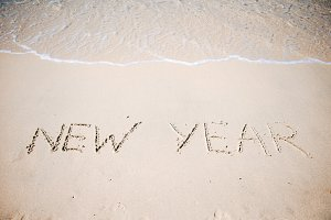 Happy New Year written in the white sand