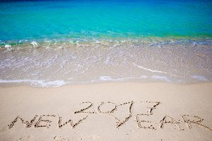 2017 New Year written in the white sand