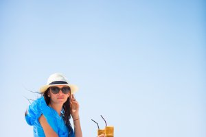 Beautiful lady drinking cold coffee enjoying sea view. Beautiful woman relax during european sea vacation on the beach enjoying frappe