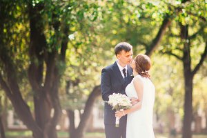 couple bride and groom on the background of the park's trees