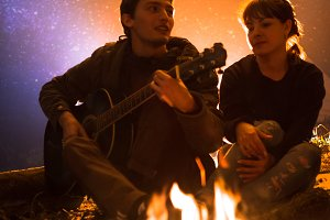 man plays guitar and woman about the fire on the background of the starry sky