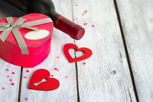 Box in shape of heart and bottle of red wine on white background