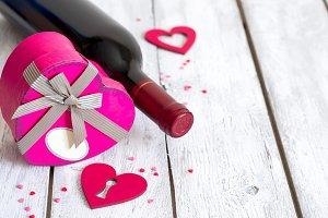 St. Valentine's setting with bottle of red wine and heart presen