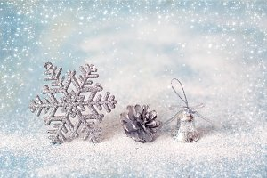 Christmas toy snowflake, fir-cone, bell on winter holiday backgr