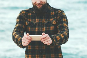 Bearded Man using Smartphone at sea