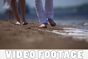 Guy and girl are walking on the sand