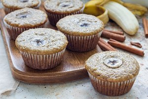 Freshly baked homemade banana cinnamon muffins with slice of banana on top, on wooden board, horizontal