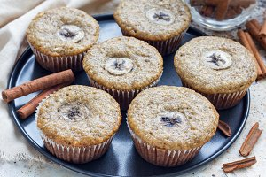 Freshly baked homemade banana cinnamon muffins with slice of banana on top, on the tray
