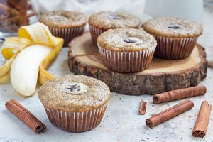 Freshly baked homemade banana cinnamon muffins with slice of banana on top, on wooden board
