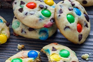 Shortbread cookies with multi-colored candy and chocolate chips on wooden table, vertical