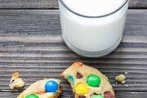 Shortbread cookies with multi-colored candy and chocolate chips, served with glass of milk, vertical