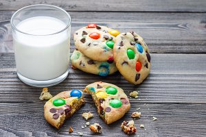 Shortbread cookies with multi-colored candy and chocolate chips, served with glass of milk, horizontal, copy space
