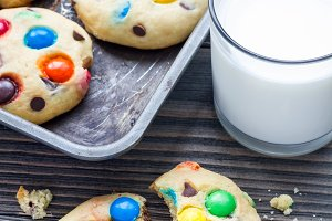 Shortbread cookies with multi-colored candy and chocolate chips on metal tray, vertical