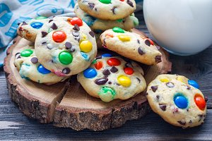 Shortbread cookies with multi-colored candy and chocolate chips on wooden board, horizontal