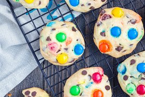 Shortbread cookies with multi-colored candy and chocolate chips on cooling rack, vertical, top view