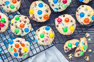 Shortbread cookies with multi-colored candy and chocolate chips on cooling rack, horizontal, top view