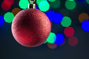 Red christmas ball hanging on gold ribbon with colorful bokeh background, copy space