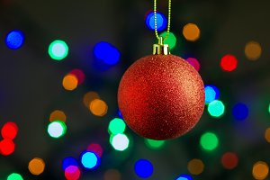 Red christmas ball hanging on gold ribbon with colorful bokeh background