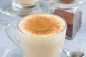 Healthy rooibos red tea latte topped with cinnamon, in glass cup and ingredients on background, vertical