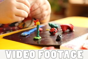 Kid sculpts figures of plasticine
