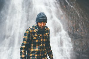 Bearded Man walking by waterfall