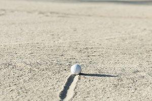 Golf ball in sand bunker.