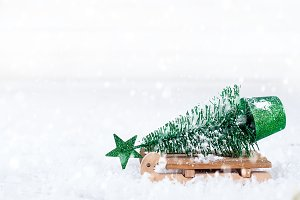wooden winter sleigh carrying a small Christmas tree