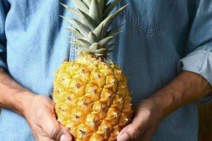 Man Holding Ripe Pineapple