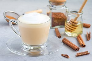 Healthy rooibos red tea latte in glass cup and ingredients on background, horizontal