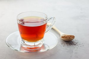 Healthy herbal rooibos red tea in glass cup, copy space