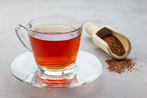 Cup of healthy herbal rooibos red tea in glass cup