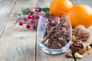 Cinnamon and anise in glass, oranges and nuts on background