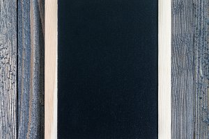 Black empty chalkboard on wooden table for copy space, vertical