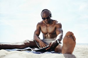 Young man sitting on beach reading