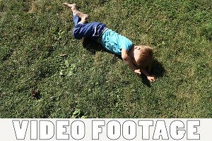 Kids somersault on grass lawn