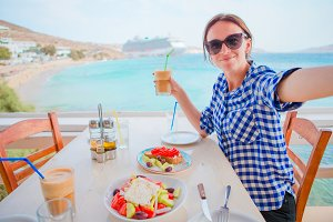 Young woman having lunch with delicious fresh greek salad, frappe and brusketa served for lunch at outdoor restaurant with beautiful view on the sea and port