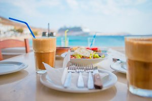 Frappe on the table background sea and big lainer. Summer iced coffee frappuccino in a tall glass and greek salad in beach bar