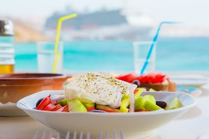 Traditional lunch with delicious fresh greek salad and brusketa served for lunch at outdoor restaurant with beautiful view on the sea and port