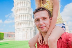 Family portrait background the Learning Tower in Pisa. Pisa - travel to famous places in Europe.