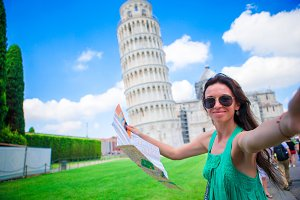 Young happy girl taking selfie background famous Pisa Tower. Tourist traveling visiting The Leaning Tower of Pisa.