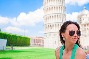 Young happy girl with toristic map on travel to Pisa. Tourist traveling visiting The Leaning Tower of Pisa.