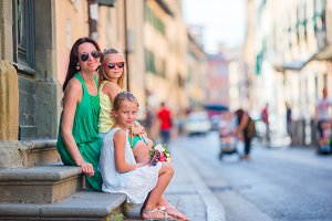 Happy mother and little adorable girls on cozy street during italian vacation. Family european vacation.