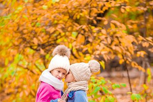 Little adorable girls playing in beautiful autumn park outdoor