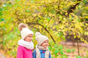 Cute little girls in colorful coats in beautiful autumn day outdoors