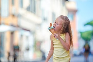 Adorable little girl eating ice-cream outdoors at summer in the city