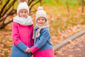 Two adorable girls in the park at warm sunny autumn day