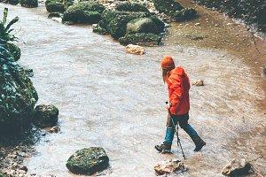 Traveler hiking crossing stream